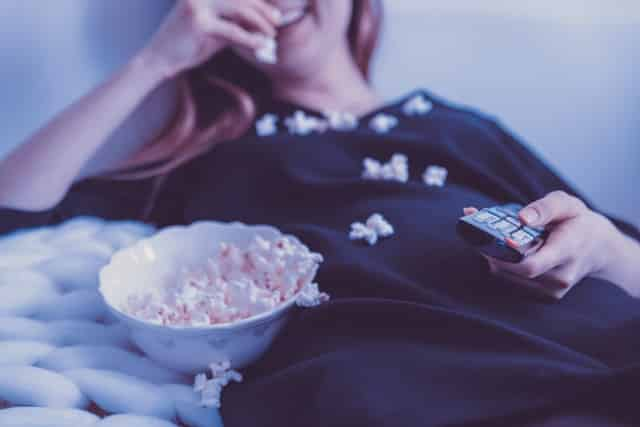 girl eating popcorn and watching movies
